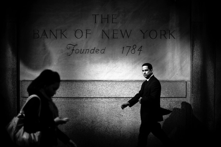 A businessman walks by the Bank of New York in Midtown Mahattan, home to many of the world's banks.