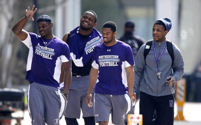 Unidentified Northwestern football players walk between their locker room and McGaw Hall, where voting is taking place on the student athlete union question...