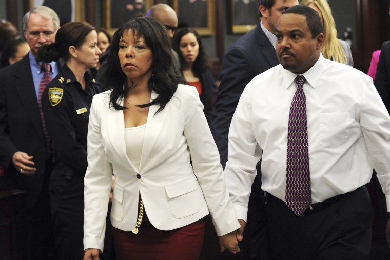 Jordan Davis' mother, Lucia McBath (C) leaves the courtroom with her husband Curtis McBath (R) as court recessed for the jury to reconsider the first charge against Michael Dunn in Jacksonville, Fla., Feb. 15, 2014.