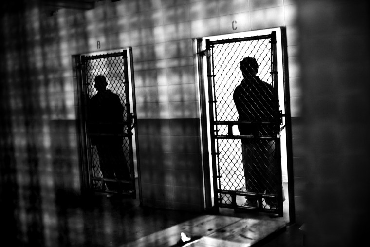 Prisoners behind a fence in solitary confinement cells in Illinois.