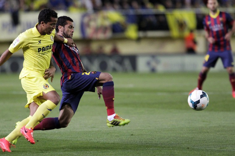 Barcelona's Dani Alves and Villarreal's Giovani Dos Santos fight for the ball during their Spanish first division soccer match at the Madrigal stadium in Villarreal on April 27, 2014.