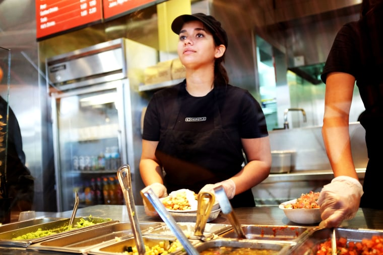 A restaurant worker fills an order at a Chipotle restaurant on March 5, 2014 in Miami, Florida.
