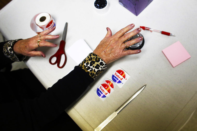 A volunteer poll worker rings a bell to count votes at a polling station on November 6, 2012 in Richmond, Wisconsin.