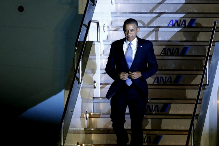 U.S. President Barack Obama walks down the steps of Air Force One as he arrives at Haneda International Airport in Tokyo on April 23, 2014.