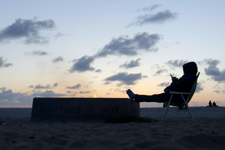 A woman sits by an open fire at Moonlight Beach as she reads messages on her phone after sunset in Encinitas, California, March 31, 2014.