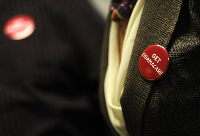 Associates at Community Health Center wear buttons during a session to enroll people in the nation's new health insurance system Oct. 1, 2013, in New Britain, Conn.