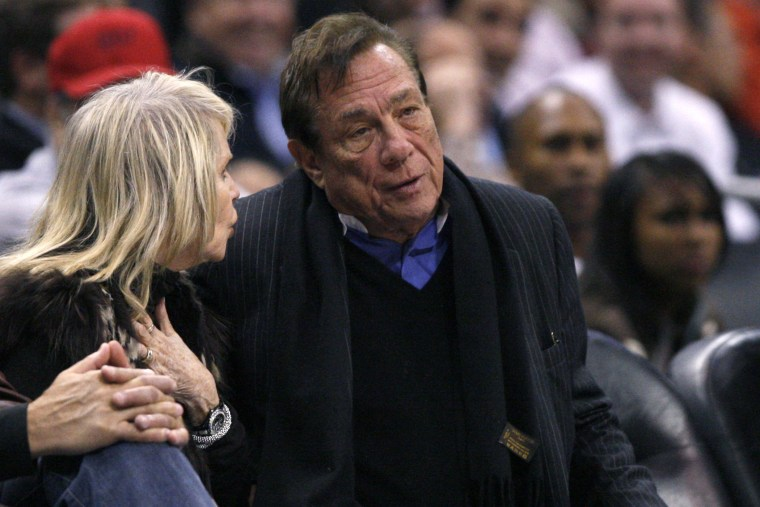 Los Angeles Clippers owner Donald Sterling sits with an unidentified companion as he watches the team play New York Knicks.