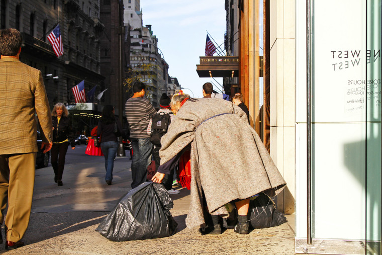 A homeless women walks among shoppers on 5th Avenue in Manhattan.
