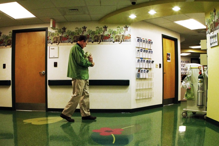 A volunteer cuddler walks the hallway with a baby at East Tennessee Children's Hospital in Knoxville. The baby is one of many infants born dependent on drugs being treated at the facility, March 29, 2013.