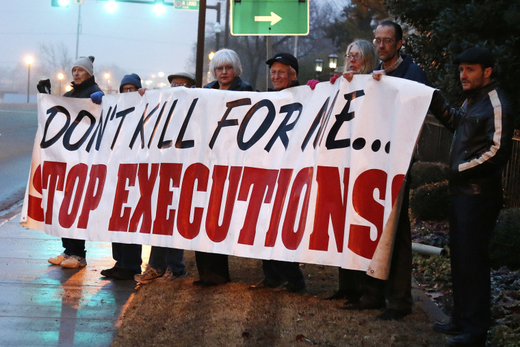 Death penalty opponents hold a sign outside the Governor's mansion in Oklahoma City, Jan. 9, 2014.