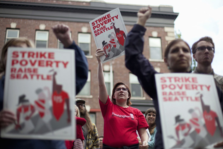 Joelle Craft (C) holds a sign during a rally and strike aimed at the fast-food industry and the minimum wage in Seattle, Washington, Aug. 29, 2013.