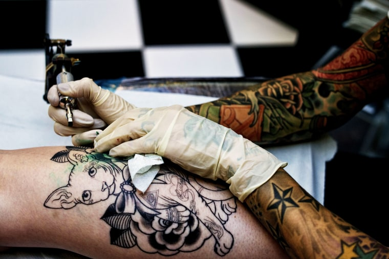 A tattoo artist works on a client at the The Family Business Tattoo parlor.