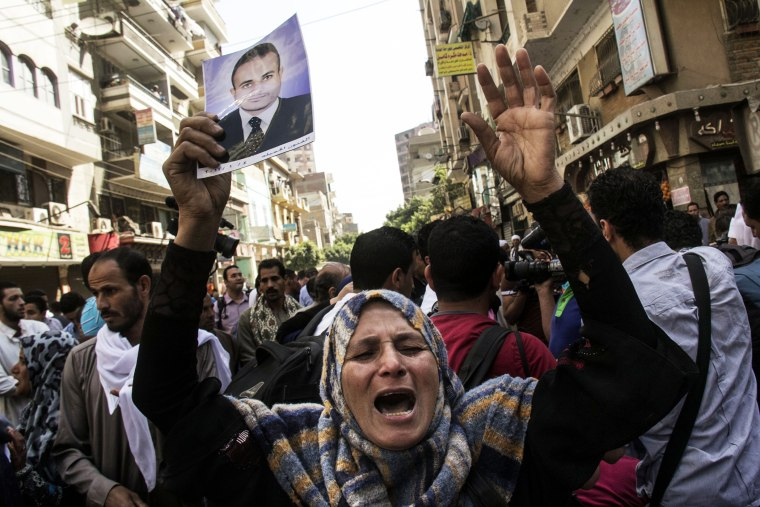 An Egyptian woman holds a photo of her son after a judge sentenced to death 683 alleged supporters of the country's ousted Islamist president in the latest mass trial in the southern city of Minya, Egypt, April 28, 2014.