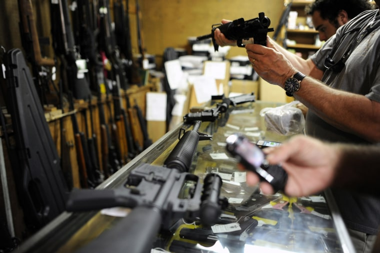 Customers look over the last two AR-15 style rifles for sale inside the Bullet Hole gun shop in Sarasota, Fla., Jan. 16, 2013.