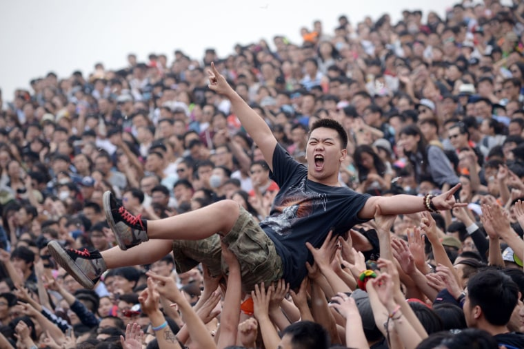 A crowd surfer gestures during the Strawberry Music Festival in Beijing on May 1, 2014.