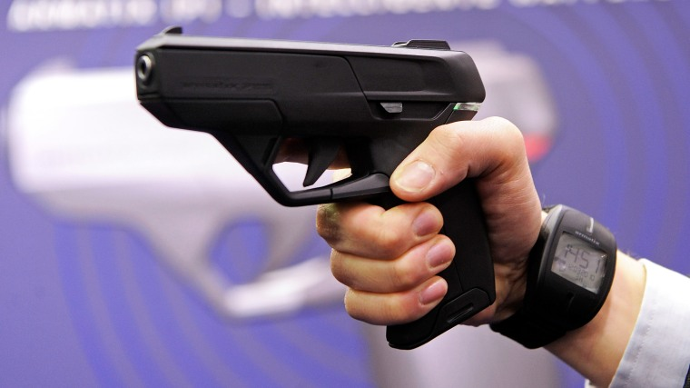 """An employee of Armatix poses for photographers as he presents the """"SmartGun Concept""""."""