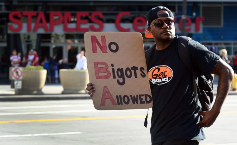 A man carries a message as people gathered to protest outside Staples Center, April 29, 2014 in Los Angeles, California.