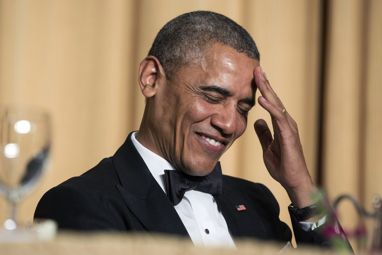 President Barack Obama rubs his head as he laughs at a joke during the White House Correspondents' Association Dinner in Washington May 3, 2014.