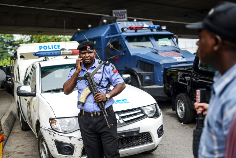 Nigerian security forces stand guard as demonstrators march during a rally to demand the government rescue schoolgirls abducted by suspected Boko Haram militants two weeks ago, in Lagos, Nigeria, May 01, 2014.