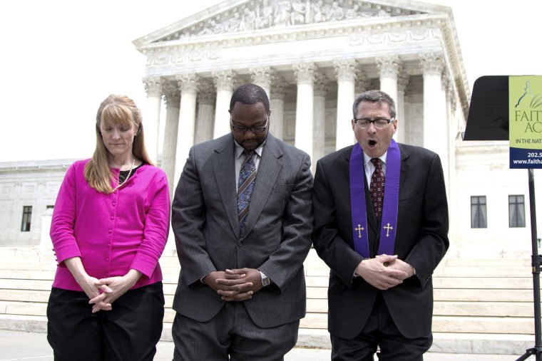 Rev. Dr. Rob Schenck, of Faith and Action, right, prays in front of the Supreme Court with Raymond Moore, center and Patty Bills, both also of Faith and Action, during a news conference, on May 5, 2014, in Washington.