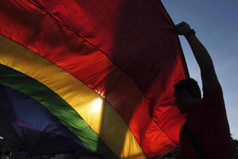 A gay rights activist holds a rainbow flag.