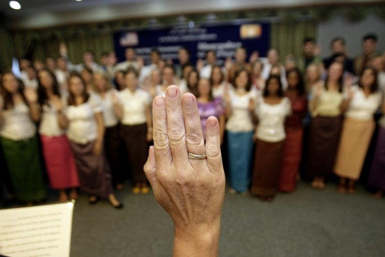 U.S. Peace Corps volunteers raise their hands to swear in during a ceremony in Phnom Penh, Cambodia, on Oct. 3, 2011.