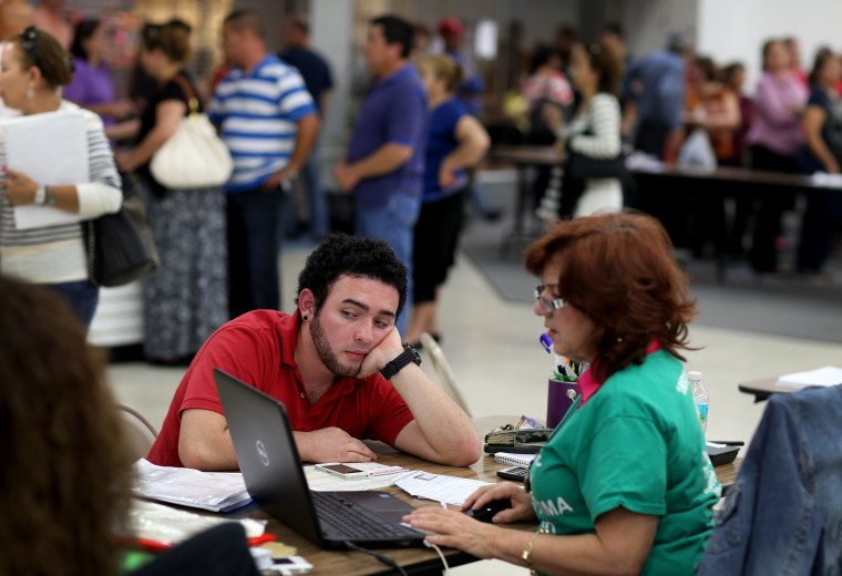Andres Cuartas sits with an agent with Sunshine Life and Health Advisors as he purchases a health insurance plan under Obamacare in Miami, March 31, 2014.