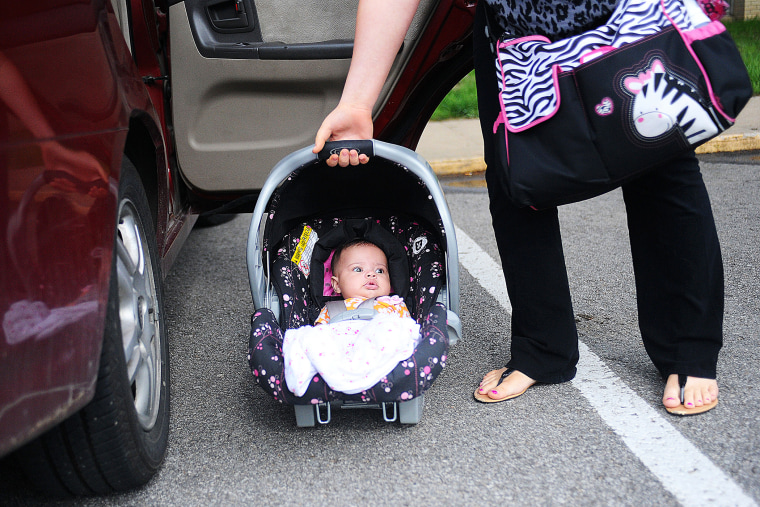 18 year-old mother Kasiyah Buckner lifts her daughter into her car outside of St. Paul Lutheran in St. Joseph, Mo., May 9, 2013.