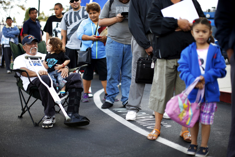Juan Ortiz, 67, and his eighteen-month-old grandson Joshua Lopez wait in line at a health insurance enrolment event in Commerce, California, Mar. 31, 2014.