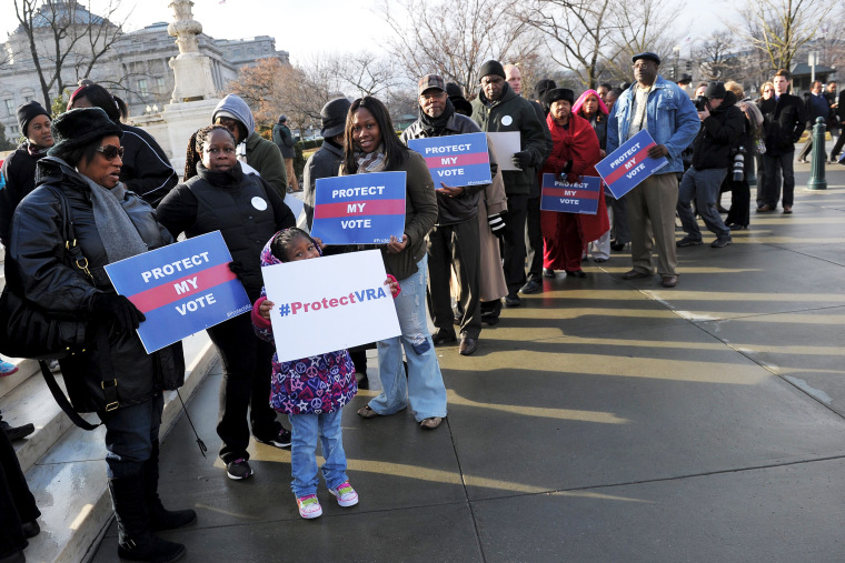 Activists hold pro-voting rights placards outside of the US Supreme Court, Feb. 27, 2013.