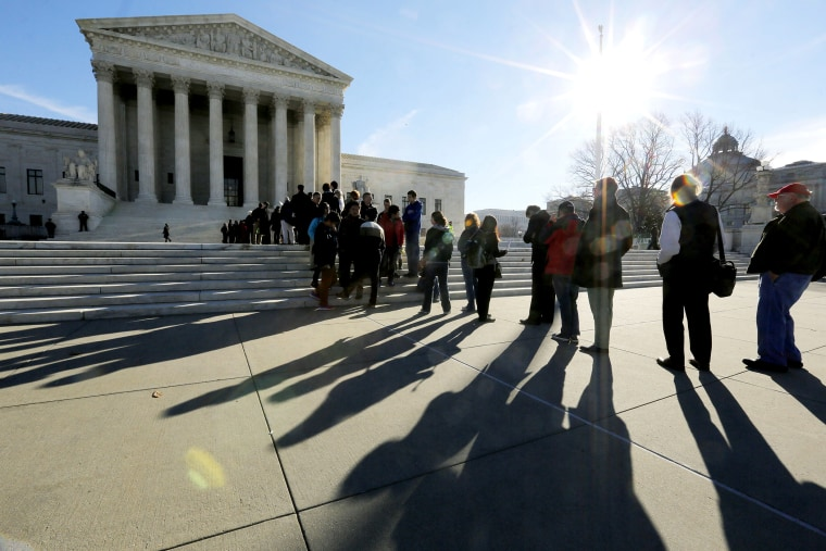 Members of the public cast shadows as they line up in front of the U.S. Supreme Court in Washington