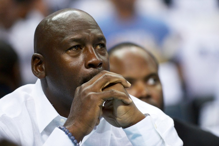 Michael Jordan watches as the Charlotte Bobcats play the Miami Heat, April 26, 2014 in Charlotte, North Carolina.