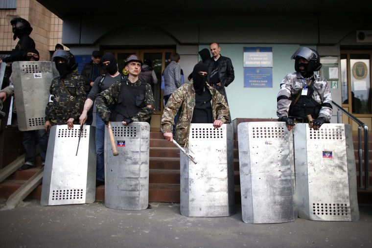 Pro-Russia protesters stand guard at the entrance of the district council building in Donetsk