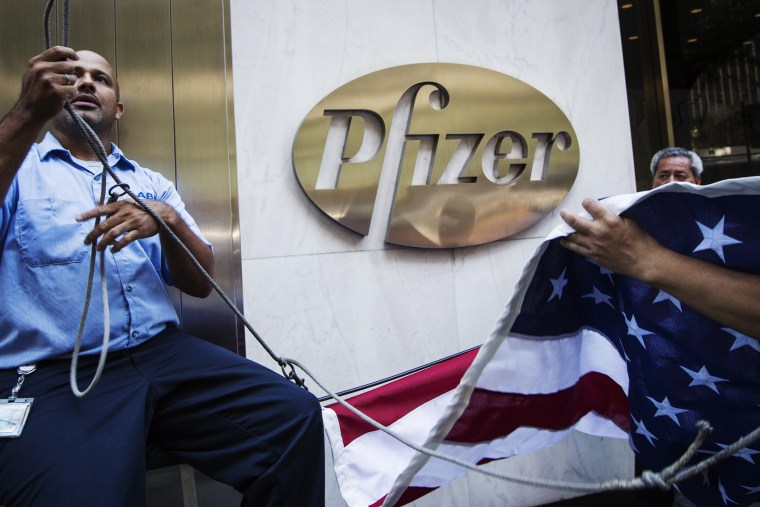 Workers raise a U.S. flag outside the Pfizer building in New York on Sept. 4, 2013.