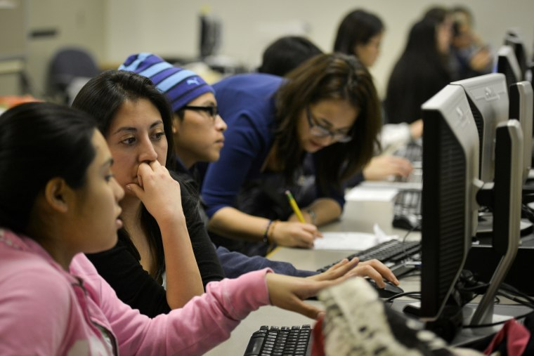 Daniela Martinez, 2nd from L, reads the college essay of undocumented high school student Seila, the only name she wishes to use, at Washington Lee High School on Jan. 23, 2014, in Arlington, VA.