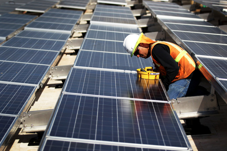 A worker finishes installing solar panels funded by federal stimulus funds atop a government building.