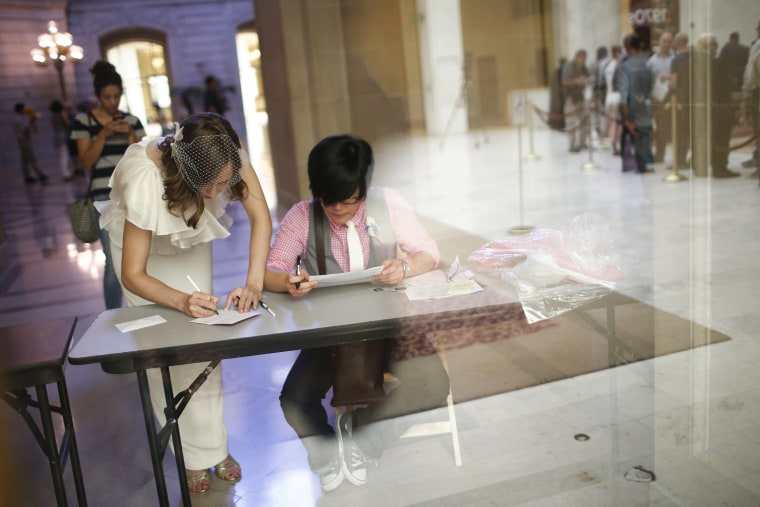Ashlee Meyer (L) and partner KY Choi sign their marriage license while others wait in line to get married at City Hall in San Francisco, Calif. June 29, 2013.