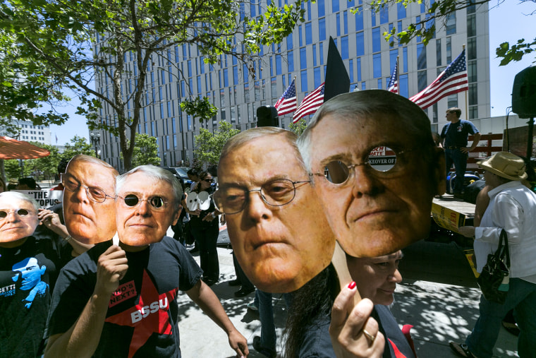 """Members of the \""""Save Our News'' coalition protest with images of billionaire brothers Charles and Bill Koch in Los Angeles Wednesday, May 29, 2013."""