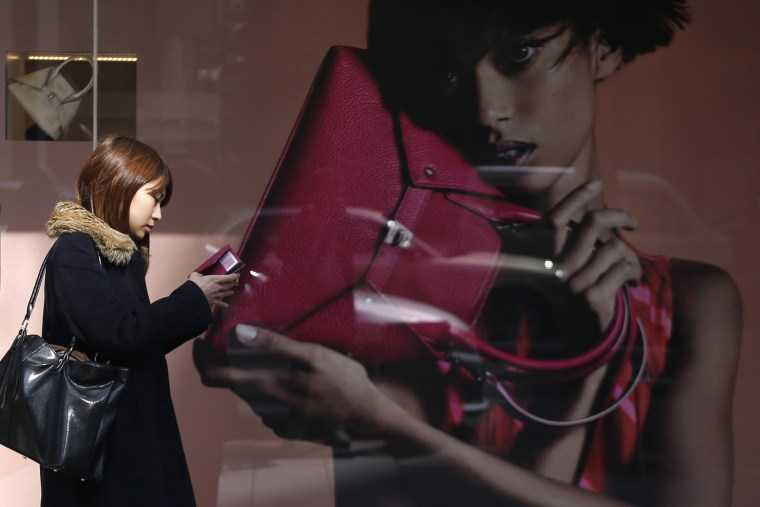 A woman looks at her mobile phone while walking past the display window of a luxury store at Ginza shopping district in Tokyo on Feb. 28, 2014.