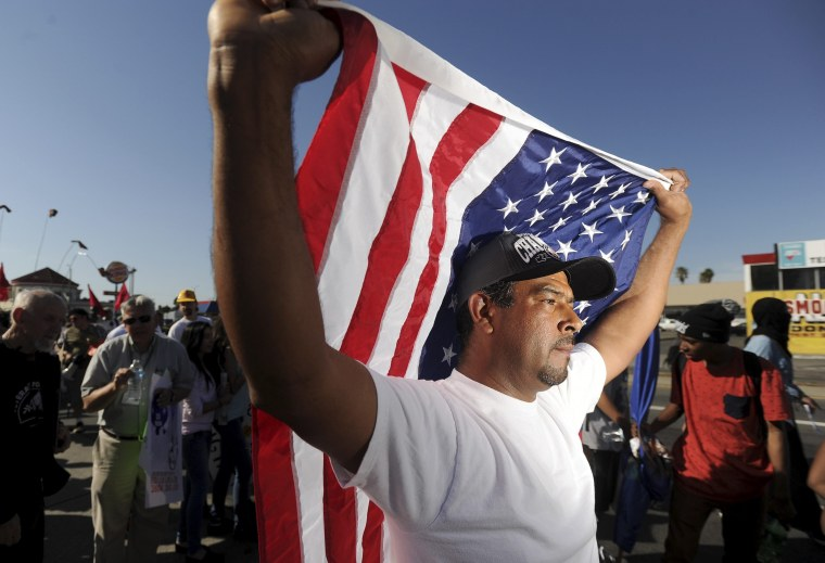 Oscar Rojas carries an American flag during a May Day demonstration in Oakland, California May 1, 2014.