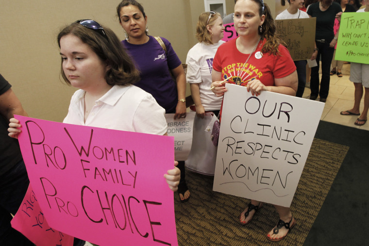 Protesters hold signs as they arrive for the start of a State Board of Health meeting in Richmond, Va.,  on June 15, 2012.
