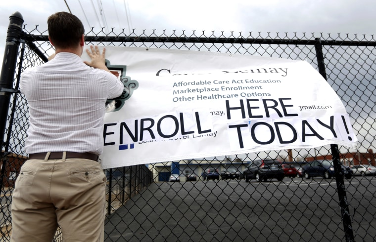 Ryan Witt hangs a sign outside offering assistance signing up for health insurance in St. Louis, March 31, 2014.