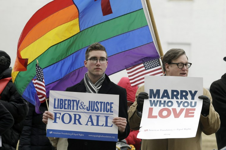 Spencer Geiger, left, of Virginia Beach, and Carl Johanson, of Norfolk, hold signs as they demonstrate outside  Federal Court in Norfolk, Va on Feb. 4, 2014.