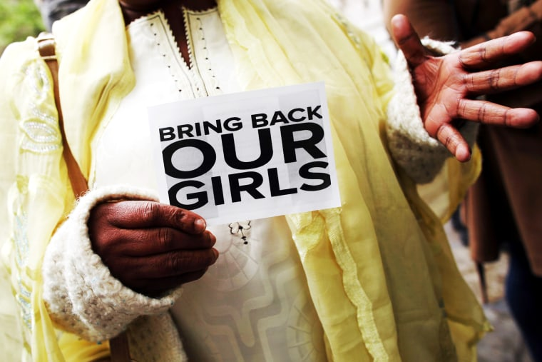A woman holds a sign that reads 'Bring back our girls' during a protest.