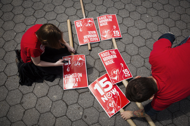 Demonstrators prepare signs supporting the raising of the federal minimum wage during May Day demonstrations in New York on May 1, 2014.