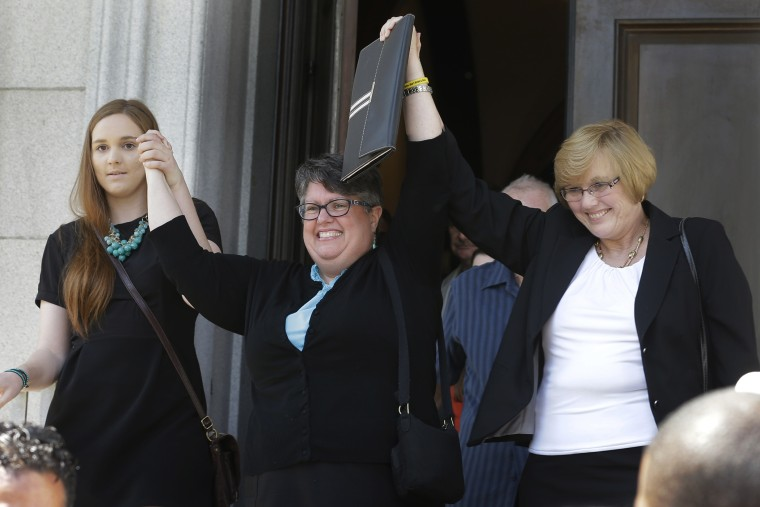 Plantiffs in the federal suit over Virginia's ban on gay marriage, Emily Schall-Townley, left, Carol Schall, center, and Mary Townley, raise their arms after a hearing on Virginia's same sex-marriage ban in Richmond, Va., on May 13, 2014.