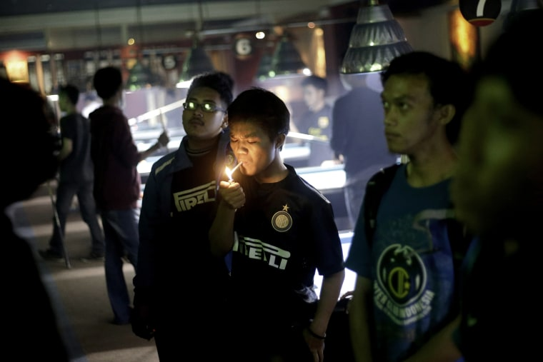 A soccer fan lights up a cigarette while watching a match at a cafe in Jakarta, Indonesia, on Oct. 27, 2013.