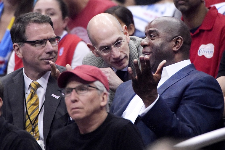 NBA Commissioner Adam Silver talks with Magic Johnson as the Los Angeles Clippers play the Oklahoma City Thunder, May 11, 2014.