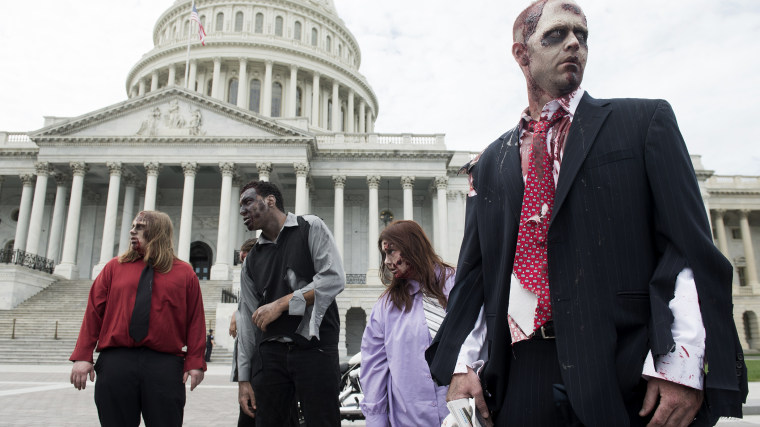 """People dressed as zombies stumble across the East Plaza of the U.S. Capitol to promote \""""The Warehouse: Project 4.1\"""" haunted house in Rockville, Md., on Oct. 3, 2012."""