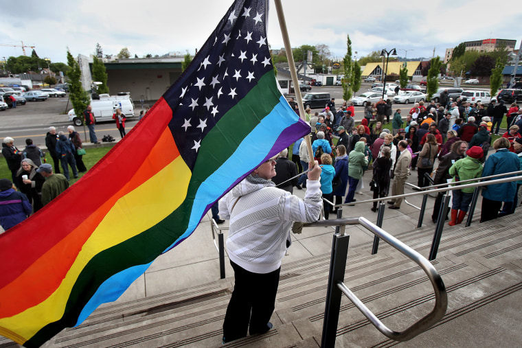 Teresa Shelley waves a rainbow-colored American flag on the steps of The Wayne L. Morse United States Courthouse on April 22, 2014 in Eugene, Ore.